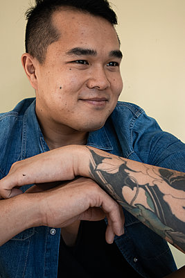 Young man with tattoo on his arm - p1640m2245942 by Holly & John