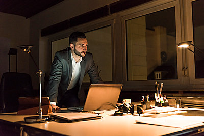 Businessman working in office at night - p300m1581535 by Uwe Umstätter