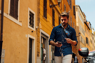 Businessman using earphones and cell phone outdoors - p300m2069401 von Boy photography