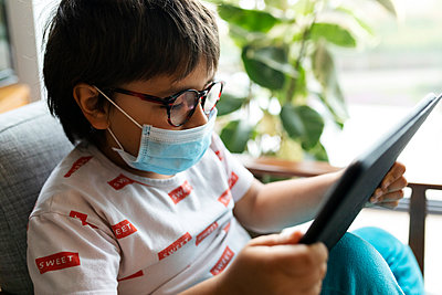 Boy with surgical mask sitting on armchair using digital tablet - p300m2189191 by Valentina Barreto