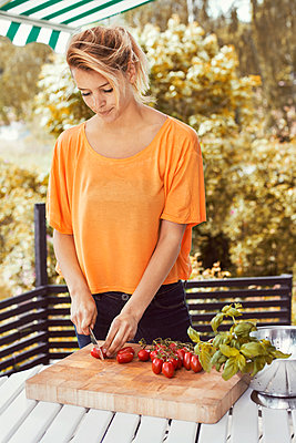 Young woman slicing tomatoes on cutting board at yard - p426m977482f by Maskot