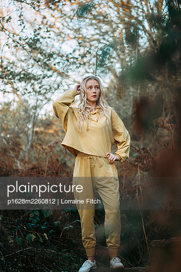 Blonde woman with curly hair and a yellow tracksuit - p1628m2260812 by Lorraine Fitch