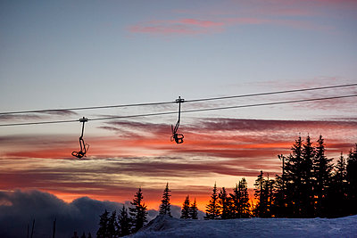 Low angle view of ski lift against cloudy sky during sunset - p1166m1486118 by Cavan Images