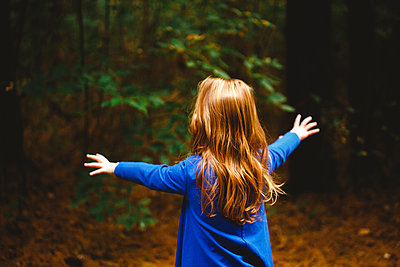 A small girl throws out arms to embrace the dark woods in front of her - p1166m2151942 by Cavan Images
