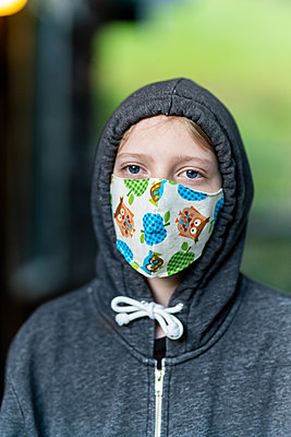 Tween wearing homemade face mask during COVID-19 Pandemic with hoodie - p1166m2201948 by Cavan Images