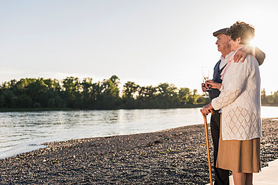 Senior couple on the beach with Champagne glasses at sunset - p300m1459832 by Uwe Umstätter