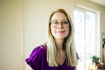 Portrait of smiling blond mature woman wearing glasses - p300m1587691 by Robijn Page