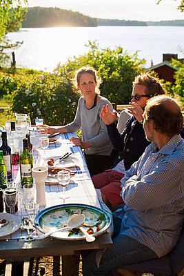 Friends having meal outdoors - p312m746605 by Jakob Fridholm