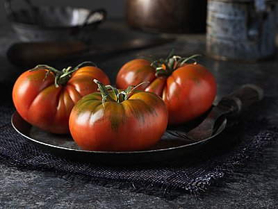 Red beef tomatoes on vintage metal plate - p429m1118549f by Diana Miller