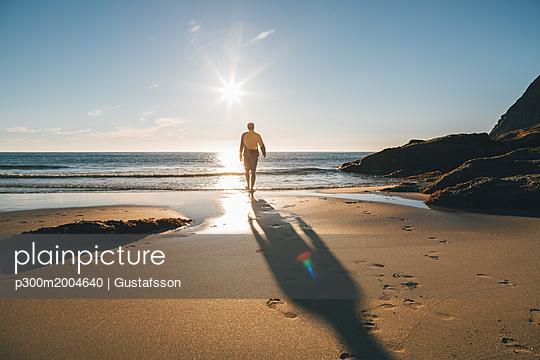 Norway, Lofoten, Moskenesoy, Man walking into the sun at Kvalvika Beach - p300m2004640 von Gustafsson