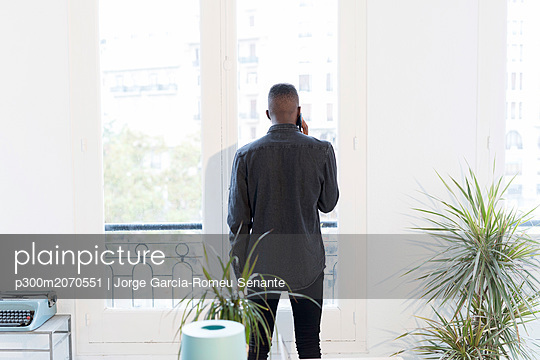 Back view of businessman on the phone in the office looking out of window - p300m2070551 von Jorge Garcia-Romeu Senante