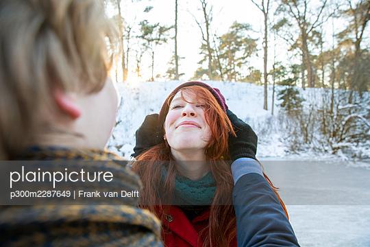 Smiling girlfriend enjoying weekend with boyfriend during winter - p300m2287649 by Frank van Delft