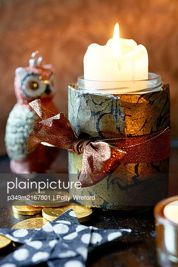 Lit candle tied with gold paper and ribbon  - p349m2167801 by Polly Wreford