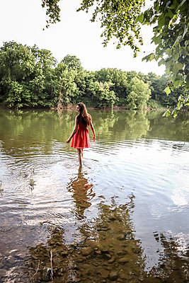 Woman in red dress standing in river - p1019m2099998 by Stephen Carroll