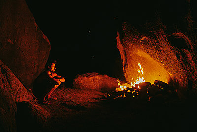 Young man in front of camp fire at night in northern California. - p1166m2202076 by Cavan Images