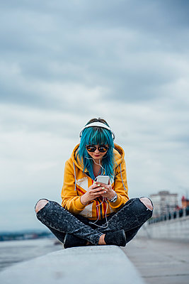 Young woman with dyed blue hair sitting on a wall listening music with headphones and smartphone - p300m2062984 von Vasily Pindyurin