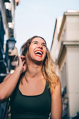 Portrait of laughing woman in the city - p300m2139744 von Jesús Martinez