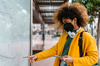 Valencia, Spain. Young woman with afro hair, looking at the map of the city. - p300m2265820 von Ezequiel Giménez