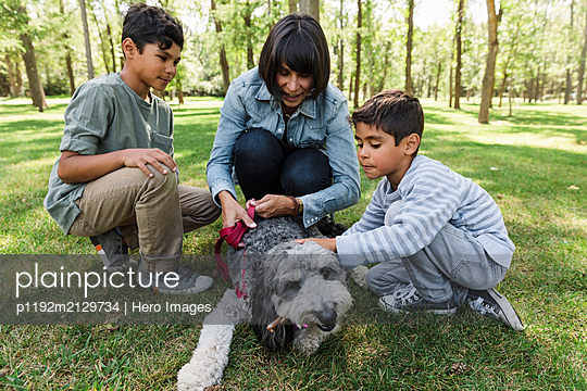 Mother with two sons and dog in urban park - p1192m2129734 by Hero Images