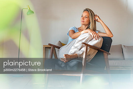 Thoughtful woman with hand in hair looking away while sitting on chair at home - p300m2276458 by Steve Brookland