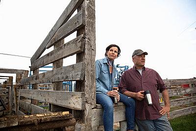 Farmer couple taking coffee break on farm - p1192m2109656 by Hero Images