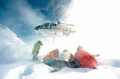 Skifahrer kauern im Rotorwind nach Ausstieg beim Heliskiing, Chugach Powder Guides, Girdwood, Alaska, USA - p1316m1160957 von Michael Neumann