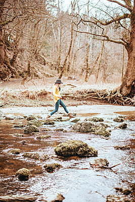 Woman is walking over some rocks in a river - p1455m2081774 by Ingmar Wein