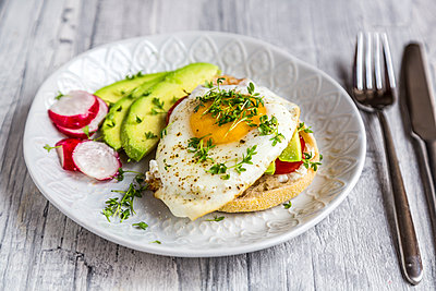 Toast with with fried egg, avocado, red radish, tomato and cress - p300m1581043 von Sandra Roesch