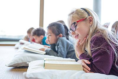Pupils lying on the floor reading books in school break room - p300m2005295 by Fotoagentur WESTEND61