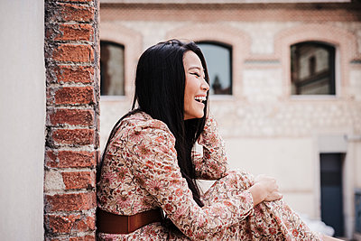 Laughing woman sitting by brick wall in city - p300m2274815 by Eva Blanco