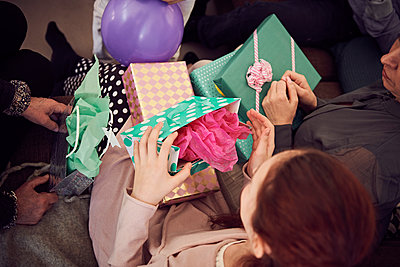High angle view of girl receiving birthday presents from family at home - p426m1580239 by Maskot