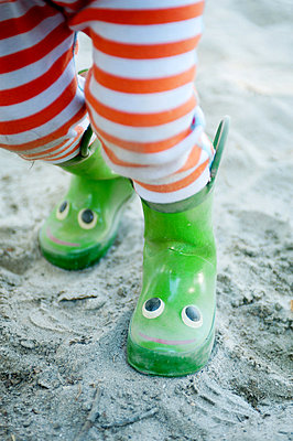Legs of young male toddler wearing smiley wellington boots - p924m825981f by Jade Brookbank