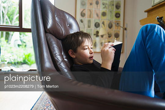Boy reading book in leather armchair - p1023m2208279 by Tom Merton