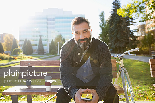 Portrait confident businessman holding cell phone on sunny urban park bench - p1192m1194205 by Hero Images