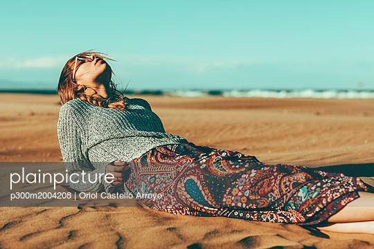 Young woman lying in desert landscape - p300m2004208 von Oriol Castelló Arroyo