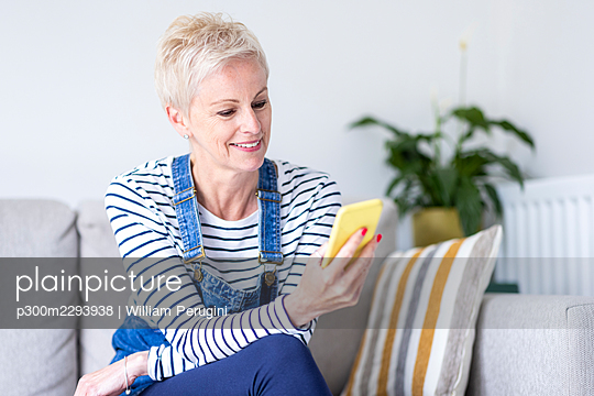 Mature woman using smart phone on sofa at home - p300m2293938 by William Perugini