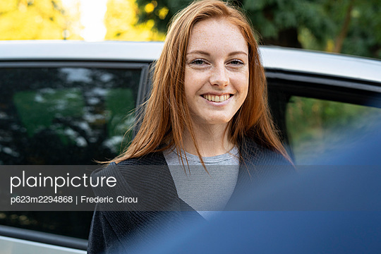 Smiling young woman standing outside a car - p623m2294868 by Frederic Cirou