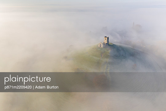 Aerial view by drone of St. Michael's Church on Burrow Mump, surrounded by a blanket of mist, Burrowbridge, Somerset, England, United Kingdom, Europe - p871m2209420 by Adam Burton
