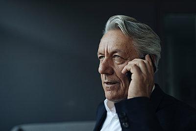 Portrait of a senior businessman talking on cell phone - p300m2140442 von Gustafsson