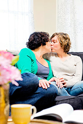 Lesbian couple kissing on sofa in living room - p555m1409077 by Shestock