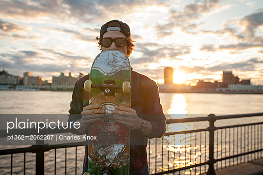 Skateboarder on wharf with cityscape behind during sunset, Montreal, Quebec, Canada - p1362m2062207 by Charles Knox