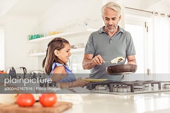 Father making fried egg for daughter at home - p300m2167516 by Floco Images