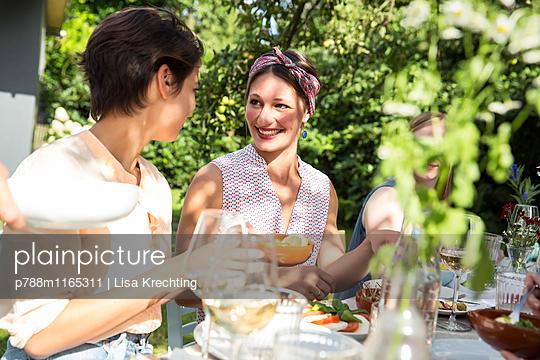 Gespräch unter Freunden auf einer Gartenparty - p788m1165311 von Lisa Krechting