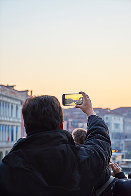 Man taking a picture of the sunset with smartphone - p1312m1575231 by Axel Killian