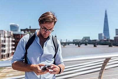 UK, London, man using his smartphone on the Millennium Bridge - p300m2042788 by Marco Govel