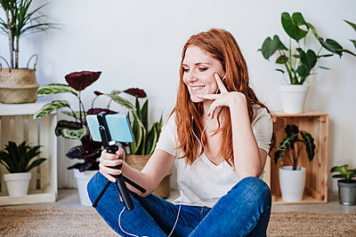 Beautiful woman smiling during video call through smart phone on floor at home - p300m2281660 by Eva Blanco