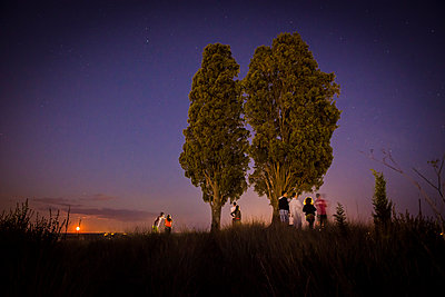 People looking at fireworks in the distance - p829m1110837 by Régis Domergue
