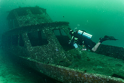Scuba diver exploring shipwreck on ocean floor - p924m2145366 by Henn Photography