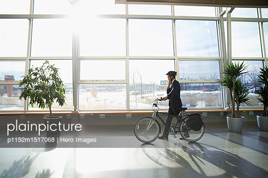 Businessman commuter in helmet walking bicycle in sunny office lobby - p1192m1517068 by Hero Images