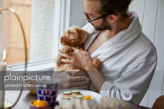 Man holding puppy - p312m2119338 by Johner